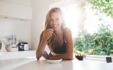 Portrait of young woman eating healthy breakfast in morning. Beautiful young woman in kitchen eating berries.