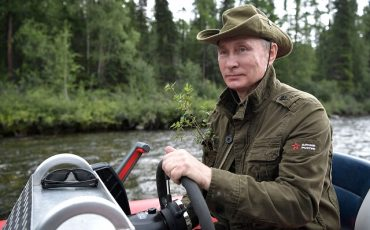 In this photo released by Kremlin press service on Saturday, Aug. 5, 2017, Russian President Vladimir Putin controls a boat during a mini-break in the Siberian Tyva region, a few days ago. (Alexei Nikolsky/Sputnik, Kremlin Pool Photo via AP)